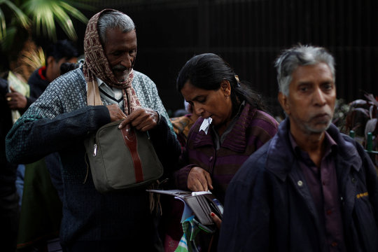 A woman checks her wallet as she stands in a queue outside the RBI to exchange her old high denomination bank notes in New Delhi