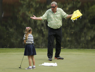 Fuzzy Zoeller of the U.S. reacts as a young girl he pulled from the crowd tries a putt during the par 3 event held ahead of the 2015 Masters at Augusta National Golf Course in Augusta