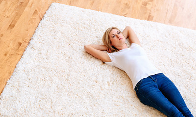 Young woman lying down on carpet