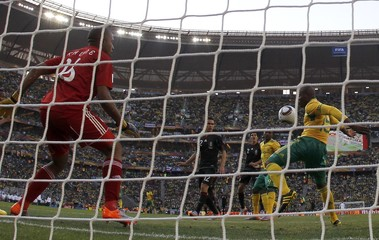 South Africa's Lucas Thwala  (R) helps his goalkeeper Itumeleng Khune (in red) to defend his goal against Mexico in the opening game during the 2010 World Cup at Soccer City stadium in Johannesburg