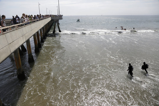 Rescue divers enter the waters near a pier for victims of a lightning strike that injured people in Venice