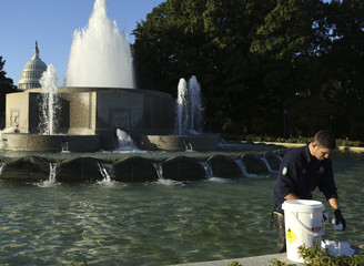 Pipe fitter Robert Kraft dispenses chlorine tablets in the Senate Garage Fountain near the U.S. Capitol in Washington