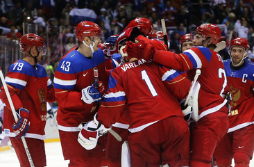 Russia's goalie Varlamov is congratulated by teammates after Russia defeated Slovakia in a shootout during their men's preliminary round ice hockey game at the Sochi 2014 Winter Olympic Games