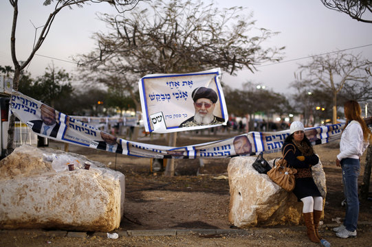 An Israeli woman sits near Shas campaign banner in Netivot