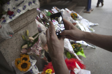 A man takes photos of cards, flowers and photos, which were left in tribute as part of a makeshift memorial on the steps in front of Joan Rivers' former residence in New York
