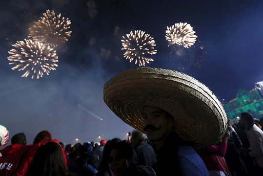 "A man wears a traditional Mexican hat as he enjoys fireworks after the ""Cry of Independence""  by Mexico's President Enrique Pena Nieto in Mexico City"