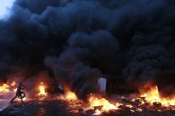 A pro-European protester prepares to throw a tyre into the flames during clashes with riot police in Kiev