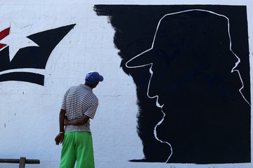 A man looks at a mural representing Cuba's late President Fidel Castro in the outskirts of Santiago de Cuba