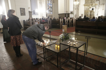 People attend a mass in the Doma church for victims of collapsed supermarket in Riga