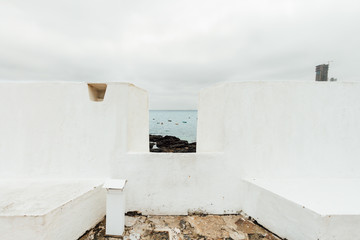 View of the sea with boats through the fort Sao Diogo wall in Salvador, Brazil