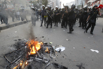 Members of the Rapid Action Battalion raid a street during a clash with activists of Jamaat-e-Islami in Dhaka