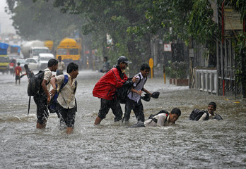 School children play on a flooded road during monsoon rains in Mumbai