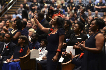 Trenisha Jackson widow of Baton Rouge police corporal Montrell Jackson stands and sings along with hymns during his funeral at the Living Faith Christian Center in Baton Rouge