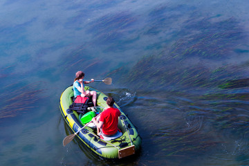 Guy and girl on rubber boat floating on amazing clear ocean backwater with algae bottom