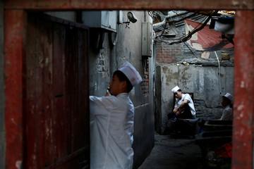 Kitchen staff sit in a back alley behind a restaurant in Beijing