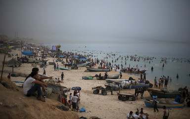 Palestinians enjoy the warm weather as others swim in the Mediterranean Sea off the coast of Gaza to cool off