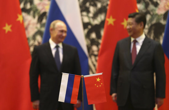 Russian and Chinese national flags are seen on the table with Russian President Putin and his Chinese counterpart Xi stand in the background during a signing ceremony at the Diaoyutai State Guesthouse in Beijing
