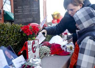 Jonna and Hunter Adams place a drawing at the statue of Stan Musial outside of Busch Stadium in St. Louis