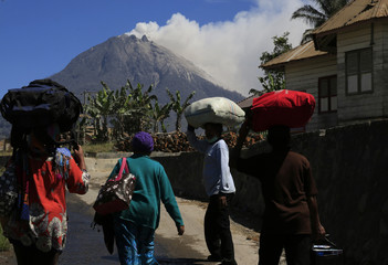 Villagers go back home after living at a temporary shelter for the last two months, as Mount Sinabung spews ash, in Karo regency, Indonesia