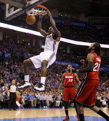 Oklahoma City Thunder center Perkins dunks the ball in front of Miami Heat Cole and Turiaf during their NBA basketball game in Oklahoma