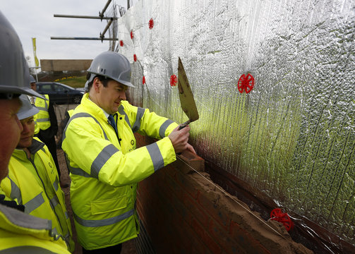 Britain's Chancellor of the Exchequer George Osborne lays a brick during a visit to a Barratt Homes building site in Nuneaton