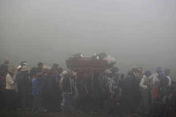 Relatives and residents carry a coffin in the fog during the funeral of 13 victims of a landslide in the village of Parrasquin