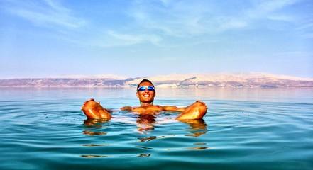 Man lies in the dead sea. Jordan on a background