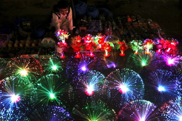 A man sells colorful lights at his stall in the market in Peshawar