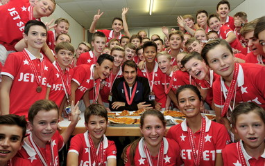 Switzerland's Federer poses together with the tournament's ball boys and girls after he won his final match against Spain's Nadal at the Swiss Indoors ATP tennis tournament in Basel