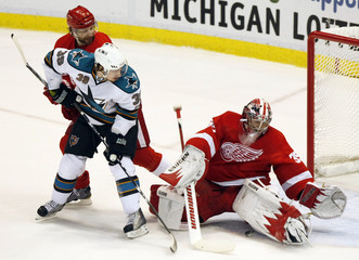 Red Wings' Stuart checks Sharks' Couture as goalie Howard makes a save in the first period during Game 6 of the NHL Western Conference semi-final hockey playoff in Detroit