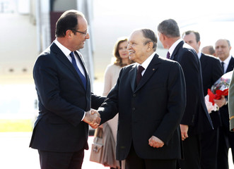 France's President Francois Hollande shakes hand with Algerian President Abdelaziz Bouteflika upon his arrival at Algiers airport