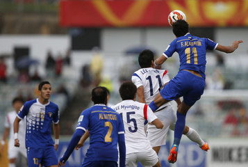 Kuwait's Fahed Al-Ebrahim and South Korea's Lee Keun-ho jump for the ball during their Asian Cup Group A soccer match at the Canberra stadium in Canberra