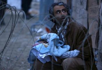 A migrant holding a baby waits at the border with Greece near Gevgelija, Macedonia