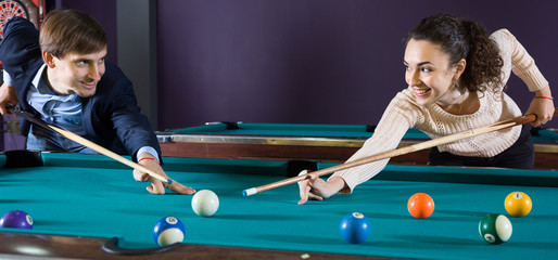 young couple playing pool looking at each other