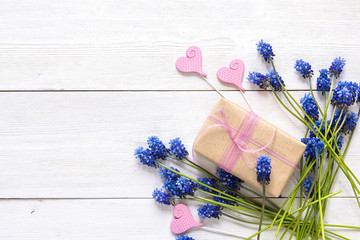 Gift box with blue muscari flowers and decorative hearts on white wooden background. Place for text.