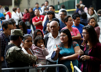 People stand in line to cast their votes in Peru's presidential election at a polling station in Lima