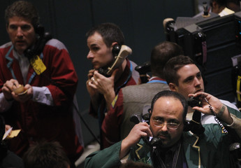 Traders work in the crude oil and natural gas options trading pit on the floor at the New York Mercantile Exchange