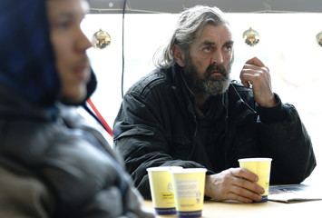 Men drink tea at one of nine temporary regional centres for the homeless, opened during the Christmas season by the chairty Crisis, in east London