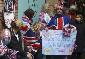 A well-wisher holds a notice congratulating Britain's Prince William and his wife Catherine, Duchess of Cambridge, on the birth of their baby dayghter, in London
