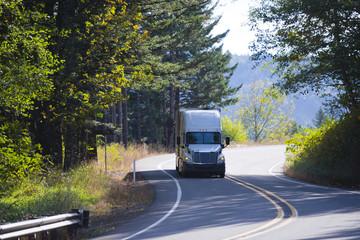 Modern semi truck on winding sunny highway with autumn trees