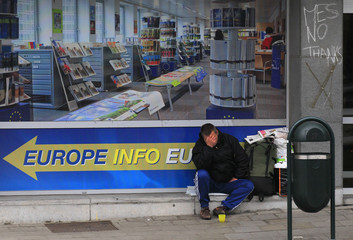 A man asks for charity while sitting outside a European Union information point in Brussels