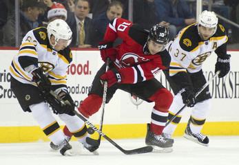 New Jersey Devils Steven Zalewski tries to control puck between Boston Bruins Brad Marchand and Patrice Bergeron in NHL game in Newark