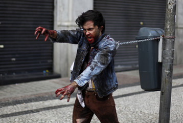 A man, made up to look like a zombie, takes part in a zombie parade in Sao Paulo