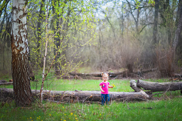 Beautiful little girl on a walk in the park in spring, summer. The girl walks through the woods, resting, having fun. A child in a pink blouse and jeans. Girl with funny tails. The girl knows the worl