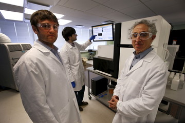 Technician Lattari works on a genetic sequencing machine as Shuldiner and Baras, co-heads of  the Regeneron Genetics Center, pose for a photo at a Regeneron Pharmaceuticals Inc. laboratory at the biotechnology company's headquarters in Tarrytown