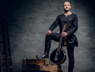 Studio image of male musicians in old traditional Celtic clothes holds vintage mandolin.