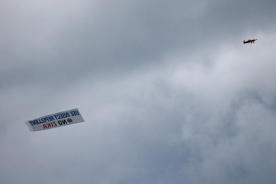 An airplane carrying a banner asking people to use insect repellent to avoid the Zika virus, flies over Miami