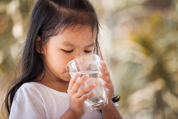 Cute asian little girl drinking fresh water from glass in vintage color tone