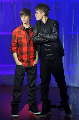 Canadian singer Justin Bieber poses with a waxwork model of himself during an official unveiling at Madame Tussauds wax museum in central London