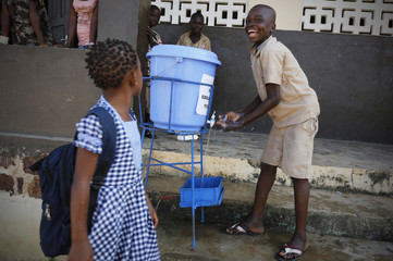 A student washes his hands with water as a preventive measure against Ebola at a hospital in Toulepleu